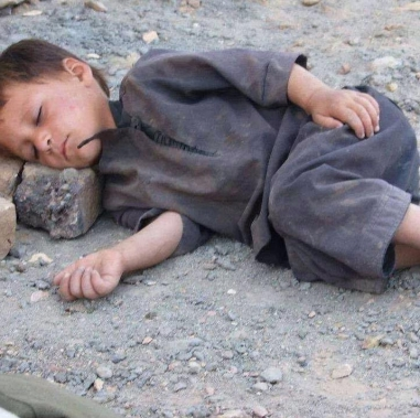 kid asleep on rock